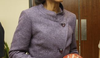 ** FILE ** Former Secretary of State Condoleezza Rice laughs after autographing a football following her visit with Cleveland Browns coaches and players at the team's training facility in Berea, Ohio, on Oct. 10, 2010. (AP Photo/Amy Sancetta)