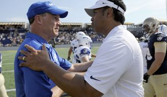 Navy head coach Ken Niumatalolo, right, meets with Air Force head coach Troy Calhoun, left, after an NCAA football game, Saturday, Oct. 5, 2013, in Annapolis, Md. Navy won 28-10. (AP Photo/Nick Wass)
