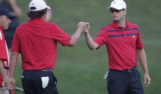 United States team players Jason Dufner, left, and Zach Johnson celebrate winning the 14th hole with a birdie during the foursomes matches at the Presidents Cup golf tournament at Muirfield Village Golf Club Saturday, Oct. 5, 2013, in Dublin, Ohio. (AP Photo/Jay LaPrete)