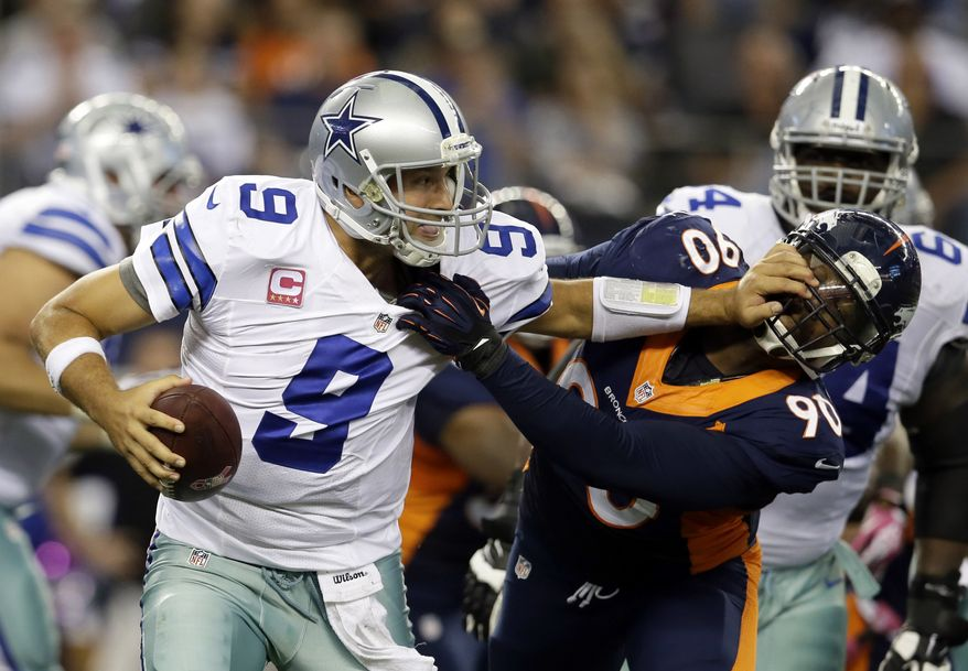 Dallas Cowboys quarterback Tony Romo (9) attempts to fight off a sack by Denver Broncos' Shaun Phillips (90) late in the fourth quarter of an NFL football game Sunday, Oct. 6, 2013, in Arlington, Texas. The Broncos won 51-48. (AP Photo/Tony Gutierrez)