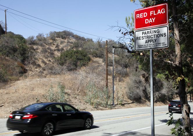 A red-flag fire-warning sign, advising hot and dry weather conditions, is posted on Friday, Oct. 4, 2013, in Pasadena, Calif. Firefighting operations in California will not be affected by the government shutdown if wildfires ignite this weekend in hot, dry and windy conditions, fire officials said Friday. (AP Photo/Nick Ut)