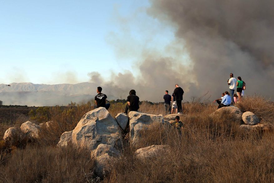 A wildfire burns in the Lake O'Neill area at Camp Pendleton, Calif., on Saturday, Oct. 5, 2013. The blaze has burned more than 1,500 acres and forced evacuation of a military housing area and the base hospital. (AP Photo/U.S. Marine Corps, Cpl. Sarah Wolff Diaz)