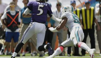 Miami Dolphins defensive end Olivier Vernon (50) grabs Baltimore Ravens quarterback Joe Flacco (5) for a sack during the first half of an NFL football game on Sunday, Oct. 6, 2013, in Miami Gardens, Fla. (AP Photo/Wilfredo Lee)