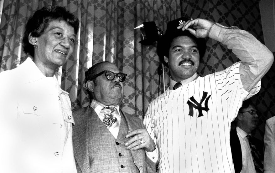 Mr. and Mrs. Martinez Jackson, left, look on as their son Reggie models his New York Yankee uniform for the press on Nov. 29, 1976 after the announcement that he signed a $3 million, five year contract with the Yanks.  (AP Photo)