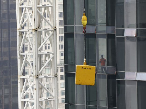 A man looks at a load stuck suspended above the street in New York, Monday, Oct. 7, 2013. Officials have closed West 57th Street between 6th and 7th avenues in Manhattan after a tower crane hoisting a load apparently got stuck about 20 floors up. A construction supervisor says the crane is the same one crane whose boom dangled dangerously nearly a year ago during Superstorm Sandy. (AP Photo/Seth Wenig)