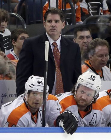 FILE - In this March 18, 2013 file photo, Philadelphia Flyers head coach Peter Laviolette watches the action from behind the bench during the second period of an NHL hockey game against the Tampa Bay Lightning, in Tampa, Fla. The Flyers fired coach Laviolette, a person familiar with the decision told The Associated Press on Monday, Oct. 7, 2013. (AP Photo/Chris O'Meara, File)