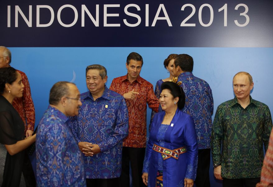 Indonesian President Susilo Bambang Yudhoyono, third from left, and his wife Ani, second from right, prepare to pose for a group photo with Russian President Vladimir Putin, right, and Mexican President Enrique Pena Nieto, center, before a dinner for the leaders of the Asia-Pacific Economic Cooperation (APEC) forum in Bali, Indonesia, Monday, Oct. 7, 2013. (AP Photo/Dita Alangkarai, Pool)