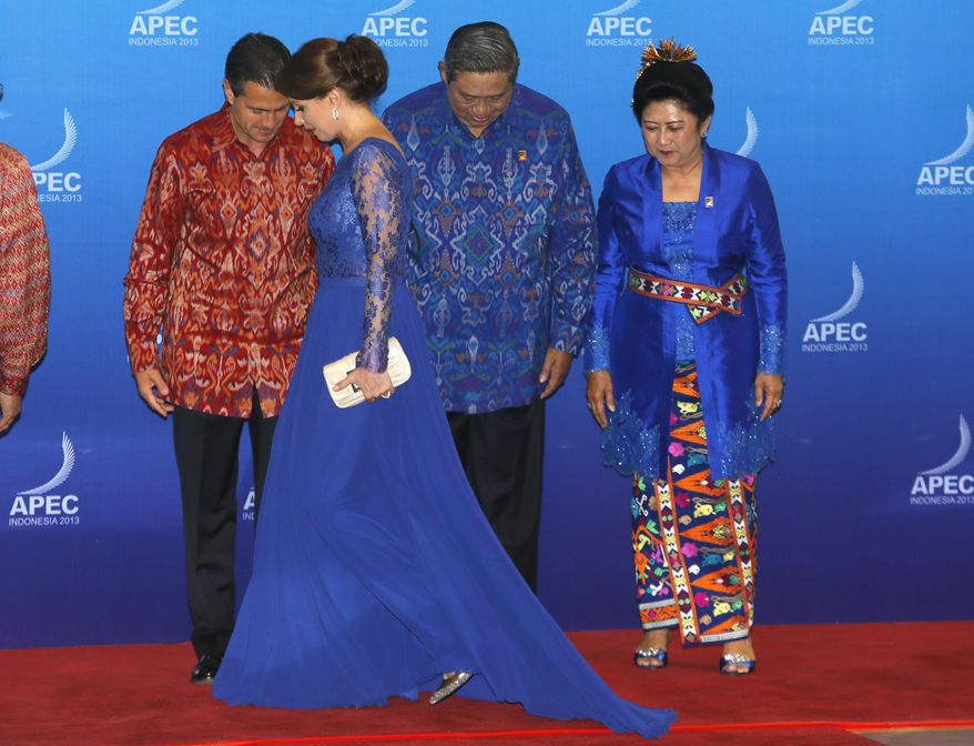 """Back left to right, Mexican President Enrique Pena Nieto, Indonesian President Susilo Bambang Yudhoyono, his wife Ani, wearing traditional Balinese """"endek"""" costume, look downwards as Nieto's wife Angelica Rivera walks to take her place beside him for a group photograph, before a dinner hosted for leaders of the Asia-Pacific Economic Cooperation (APEC) nations in Bali, Indonesia, Monday, Oct. 7, 2013. (AP Photo/Mast Irham, Pool)"""