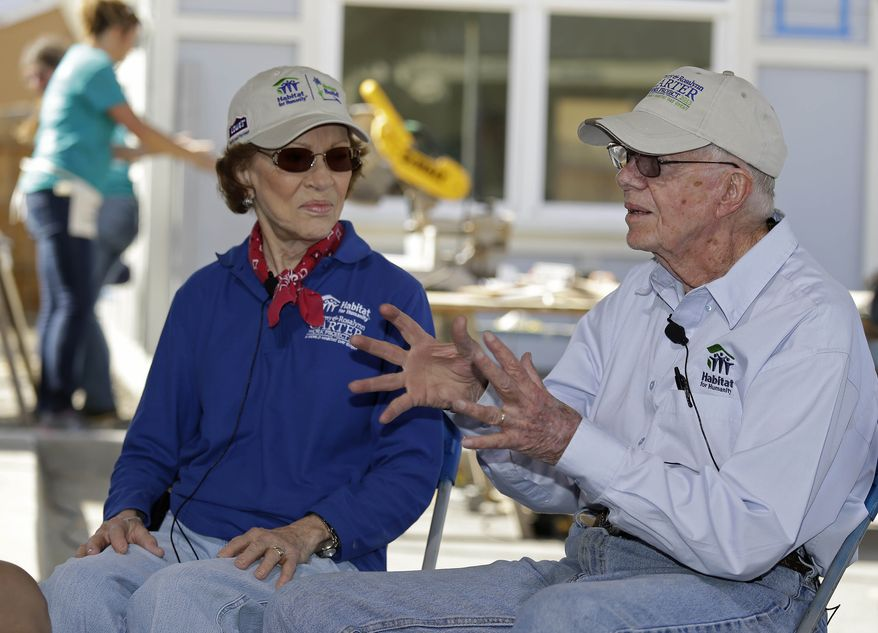 Former President Jimmy Carter and his wife, Rosalynn, answer questions during an interview at a Habitat for Humanity homesite Monday, Oct. 7, 2013, in Oakland, Calif. The former President and his wife are commemorating their three-decade-long relationship with Habitat for Humanity by wielding hammers and saws in the San Francisco Bay Area. Carter said Monday that if he were back in the White House, he would work with Republicans and Democrats to secure more funding for affordable housing and urge more flexibility in resolving differences involving the critical issue. (AP Photo/Eric Risberg)