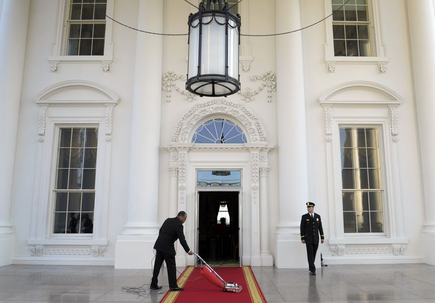 ** FILE ** In this March 14, 2012, file photo, the red carpet of the North Portico is prepared for President Barack Obama and first lady Michelle Obama to welcome Britain's Prime Minister David Cameron and his wife Samantha to the White House for a State Dinner in Washington. Now in its second week, the partial government shutdown has taken its toll on the White House. (AP Photo/Susan Walsh, File)