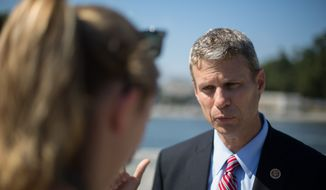 Congressman Bill Huizenga, of the 2nd District, Michigan, speaks with Reporter Meredith Somers, at the World War II memorial due to the government shutdown in Washington, DC., Wednesday, October 2, 2013.  (Andrew S Geraci/The Washington Times)