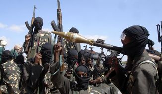 **FILE** Armed al-Shabab fighters just outside Mogadishu prepare to travel into the city in pickup trucks on Dec. 8, 2008, after vowing there would be new waves of attacks against Ethiopian troops. (Associated Press/Farah Abdi Warsameh)