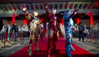 "FILE - In this Saturday, April 6, 2013 file photo, Chinese performers dressed as Iron Man pose for photos during a promotional event for the movie ""Iron Man 3"" before its release in China in early May at the Imperial Ancestral Temple in Beijing's Forbidden City. Hong Kong Disneyland is adding an Iron Man-themed area in the hopes that the Marvel superhero's success at the Chinese box office will help draw more visitors to the underachieving resort. The park said Tuesday, Oct. 8 that the Iron Man Experience is planned to open by late 2016. (AP Photo/Andy Wong, File)"