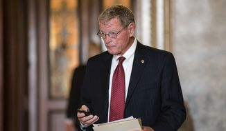 ** FILE ** Sen. James M. Inhofe, an Oklahoma Republican who is his party's ranking member on the Senate Armed Services Committee, leaves the Senate after assisting Sen. Ted Cruz, Texas Republican, with his overnight fight on the floor against the Affordable Care Act, popularly known as Obamacare, at the Capitol in Washington on Wednesday, Sept. 25, 2013. (AP Photo/J. Scott Applewhite)