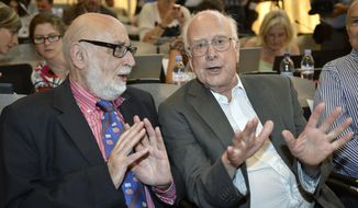 ** FILE ** In this Wednesday, July 4, 2012, file photo Belgian  physicist Francois Englert, left, and British physicist Peter Higgs right, answer journalist's question about the scientific seminar to deliver the latest update in the search for the Higgs boson at the European Organization for Nuclear Research (CERN) in Meyrin near Geneva, Switzerland. Francois Englert and Peter Higgs were awarded the Nobel physics prize on Tuesday, Oct. 8, 2013. (AP Photo/Keystone/Martial Trezzini, File)