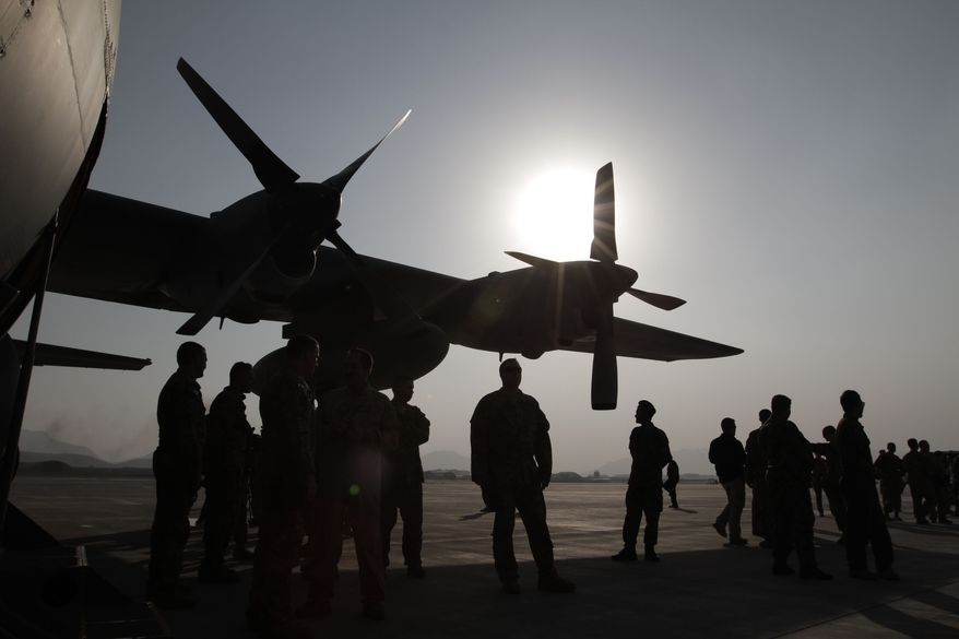 Afghan National Army and International Security Assistance Force personnel gather near a C-130 transport aircraft during a handover ceremony at the Afghan Air Force Base in Kabul, Afghanistan, Wednesday, Oct. 9, 2013. Afghanistan took delivery on Wednesday on two C-130 transport aircraft from the United States, part of an effort to give the country's military the ability to better fight insurgents around the country. (AP Photo/Rahmat Gul)