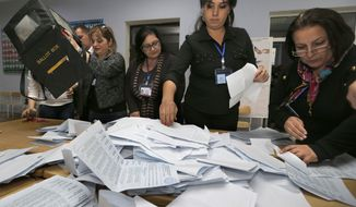 Electoral commission staff count ballot papers after voting closed at a polling station in Baku, Azerbaijan, Wednesday, Oct. 9, 2013. Azerbaijan's president won a third five-year term by a landslide in Wednesday's vote, according to an exit poll, extending decades of dynastic rule in the oil-rich Caspian Sea nation allied with the West. (AP Photo/Sergei Grits)