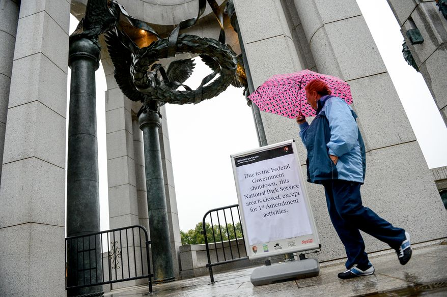 Visitors to the World War II Memorial stop to read a sign about the memorials being closed due to an ongoing government shutdown, Washington, D.C., Wednesday, October 9, 2013. (Andrew Harnik/The Washington Times)