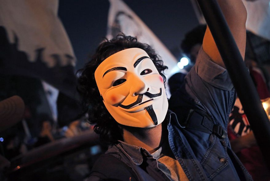 An Egyptian protester wears a mask as he attends a protest marking the second anniversary of a military crackdown on protesters outside Egypt's state TV building in Cairo, Egypt, Wednesday, Oct. 9, 2013. Hundreds of Egyptians held candles, waved pictures of slain protesters and demanded retribution from former generals while marking the second anniversary of the killing of 26 people, mostly Christians, in the military crackdown outside the state TV building. (AP Photo/Khalil Hamra)