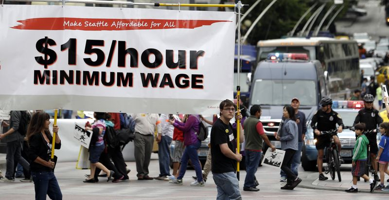 """In this photo taken, Aug. 1, 2013, demonstrators protesting what they say are low wages and improper treatment for fast-food workers march in downtown Seattle. In an interview with The Associated Press, Mayor Mike McGinn said he thought $15 was a """"fair starting point"""" for the minimum wage discussion. Washington already has the nation's highest state minimum wage at $9.19 an hour. (AP Photo/Elaine Thompson, File)"""