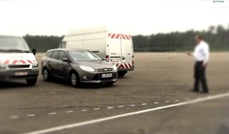 A man tests new Ford technology that allows drivers to park their vehicle from outside the car. (YouTube)