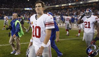 New York Giants quarterback Eli Manning (10) walks off the field after the Giants' 27-21 loss to the Chicago Bears in an NFL football game, Thursday, Oct. 10, 2013, in Chicago. (AP Photo/Charles Rex Arbogast)