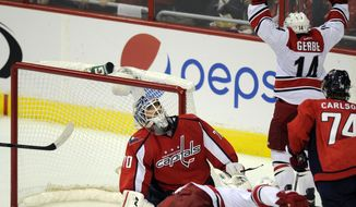 Washington Capitals goalie Braden Holtby (70) reacts after Carolina Hurricanes center Nathan Gerbe (14) scored a goal against him during the third period an NHL hockey game, Thursday, Oct. 10, 2013, in Washington. The Hurricanes won 3-2. Also seen is Washington Capitals defenseman John Carlson (74). (AP Photo/Nick Wass)