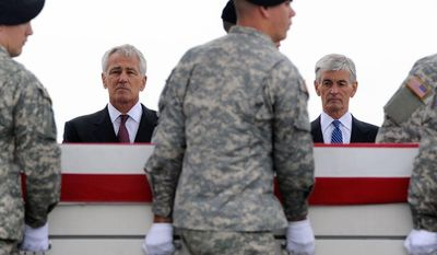 ** FILE ** Defense Secretary Chuck Hagel, left, and Army Secretary John McHugh, right, watch an Army carry team move a transfer case containing the remains of Pfc. Cody J. Patterson Wednesday, Oct. 9, 2013, at Dover Air Force Base, Del. According to the Department of Defense, Patterson, 24, of Philomath, Ore., died Oct. 6, 2013, in Zhari district, Afghanistan of injuries sustained when enemy forces attacked his unit with an improvised explosive device. (AP Photo/Steve Ruark)