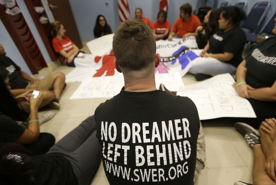 Geoff Robbins, 24, center, sits on the floor with other activists in support of immigration reform during a protest at the office of Congressman Mario Diaz-Balart, R-Fla., Friday, Oct.11, 2013, in Miami. They want Diaz-Balart to show results on immigration reform. He is one of the few Republicans still involved in bi-partisan talks. (AP Photo/Lynne Sladky)
