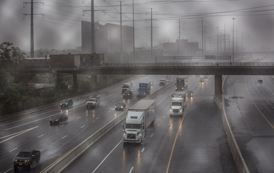 Truck drivers block traffic as they slowly drive in the rain on the Capital Beltway in Alexandria, Va., on Oct. 11, 2013, as a protest to the government shutdown. (Andrew S. Geraci/The Washington Times)
