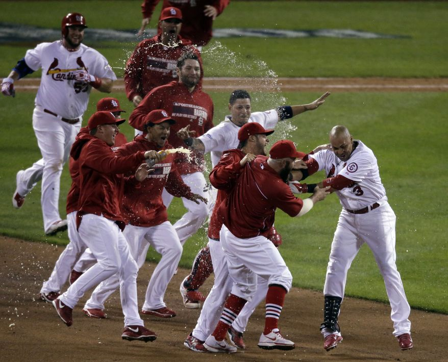 St. Louis Cardinals' Carlos Beltran is mobbed by teammates after his game-winning hit during the 13th inning of Game 1 of the National League baseball championship series against the Los Angeles Dodgers Saturday, Oct. 12, 2013, in St. Louis. (AP Photo/Chris Carlson)