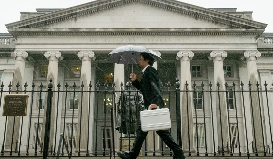 A pedestrian walks past the U.S. Treasury Building in Washington in the rain on Oct. 10, 2013. (Associated Press) **FILE**