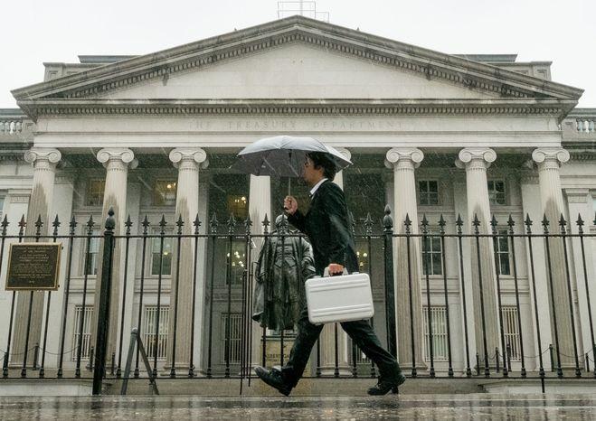 A pedestrian walks past the U.S. Treasury Building in Washington in the rain on Oct. 10, 2013. (Associated Press) **FILE**