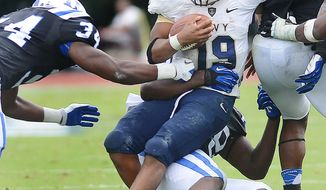 Navy quarterback Keenan Reynolds (19) is taken down by Duke's Carlos Wray, bottom, and Jonathan Woodruff (34) during an NCAA college football game Saturday, Oct. 12, 2013, in Durham, N.C.  (AP Photo/The Herald-Sun, Bernard Thomas)