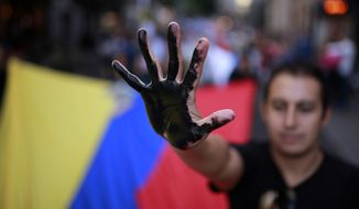 A protestor shows his black painted hand as he carries an Ecuador flag to protest against Chevron and the oil contamination in Ecuador's Amazon region during a joined global demonstration in Madrid, Spain Saturday, Oct. 12, 2013. Earlier this year, Ecuador awarded a $19 billion judgment to the residents of this area for Texaco's contamination of this rainforest between 1972 and 1990. But Chevron Corp., which bought Texaco in 2001, said it won't pay because it says Texaco dealt with the problem before it was bought. (AP Photo/Andres Kudacki)