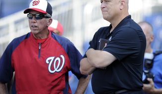 Washington Nationals manager Davey Johnson, left, talks with former Baltimore Orioles baseball play and  hall of famer Cal Ripken Jr., right, during batting practice before a baseball game against the Los Angeles Dodgers, Saturday, July 20, 2013, in Washington. (AP Photo/Nick Wass)