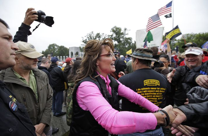 "Former Alaska Gov. Sarah Palin, arrives for a rally at the World War II Memorial in Washington Sunday, Oct. 13, 2013, to protest, as she said, how politicians used ""your hard-earned tax money to barricade the memorials"" during the federal government shutdown. She called it a ""slimdown,"" saying it only halted a small part of the ""bloated"" government. The Memorial has been closed to the public since the shutdown. (AP Photo/Alex Brandon)"