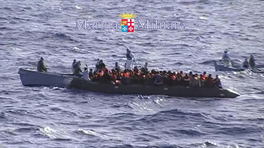 In this photo grabbed from a footage released by the Italian Navy Sunday, Oct. 13, 2013, migrants receive help from two raft from the Italian Navy ship Libra, off the Sicilian island of Lampedusa Saturday, Oct.12, 2013.  In recent days hundreds of migrants have drowned as smugglers' ship packed with migrants sank or capsized. The deaths have sharpened calls for a coordinated European response to the wave of asylum-seeker fleeing war and repression making their way to Libya to embark on a sea journey, mostly in rickety smugglers' boats en route to Italy's southernmost island of Lampedusa, just 70 kilometers (50 miles) away. Despite the perils, the boats keep coming. Authorities have rescued hundreds more at sea this weekend. (AP Photo/Italian Navy HO)
