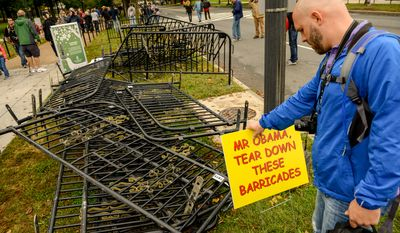 Jeff Weaver of Akron, Ohio puts up a sign after protesters removed barricades for the government shutdown, Washington, D.C., Sunday, October 13, 2013. (Andrew Harnik/The Washington Times)