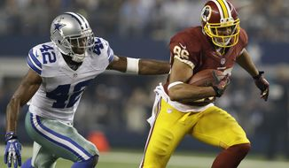 Dallas Cowboys free safety Barry Church (42) attempts to reach Washington Redskins tight end Jordan Reed (86) in the first half of an NFL football game, Sunday, Oct. 13, 2013, in Arlington, Texas. (AP Photo/LM Otero)