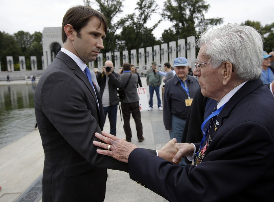 William Swenson, left, from Seattle, Wash., talks with 10th Mountain Division WWII veteran Harrison Coleman, from Novi, Mich., during a ceremony at the WWII Memorial Sunday, Oct. 13, 2013 in Washington. On Tuesday, October 15, 2013, President Barack Obama is scheduled to award the Metal of Honor to Swenson, a former active duty Army Captain, for conspicuous gallantry. The WWII memorial has been closed due to the government shutdown. (AP Photo/Alex Brandon)
