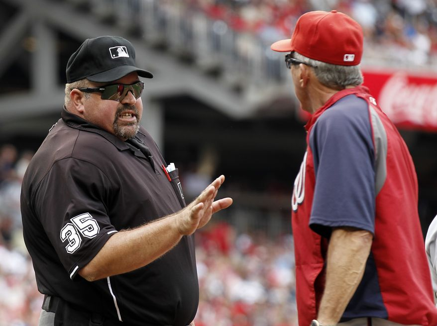 Umpire Wally Bell talks with Washington Nationals manager Davey Johnson during the second inning of a baseball game with the St. Louis Cardinals at Nationals Park Saturday, Sept. 1, 2012, in Washington. (AP Photo/Alex Brandon)