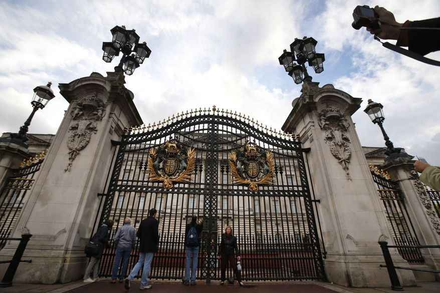 Tourists gather at the area in front of Buckingham Palace in central London, Monday, Oct. 14, 2013. British police arrested a man with a knife after he tried to dart through a gate at Buckingham Palace in London on Monday. The palace said Queen Elizabeth II was not in residence. Breaches of royal security are rare, but just a month ago police arrested two men over a suspected break-in at the palace. (AP Photo/Lefteris Pitarakis)