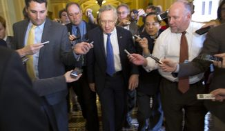 "Senate Majority Leader Sen. Harry Reid, D-Nev., is surrounded by reporters after leaving the office of Senate Minority Leader Sen. Mitch McConnell, R-Ken., on Capitol Hill on Monday, Oct. 14, 2013 in Washington. Reid reported progress Monday towards a deal to avoid a threatened default and end a two-week partial government shutdown as President Barack Obama called congressional leaders to the White House to press for an end to the impasse. ""We're getting closer,"" he told reporters. (AP Photo/ Evan Vucci)"