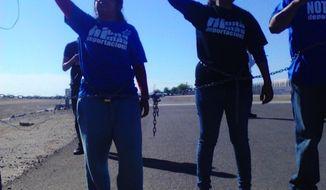 Two immigrant-rights protesters take part in an Oct. 14 demonstration in front of a detention facility in Eloy, Ariz., to try to block federal authorities from being able to deport the illegal immigrants being held there. (Courtesy of notonemoredeportation.com)