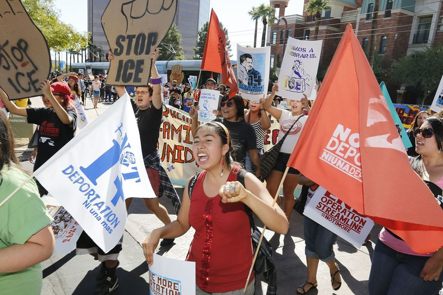 "A protester yells as she joins about 250 people as they march to the U.S. Immigrations and Customs Enforcement office with a goal of stopping future deportations on Monday Oct. 14, 2013, in Phoenix.  The protesters chanted ""no more deportations"" and ""shut down ICE."" (AP Photo/Ross D. Franklin)"