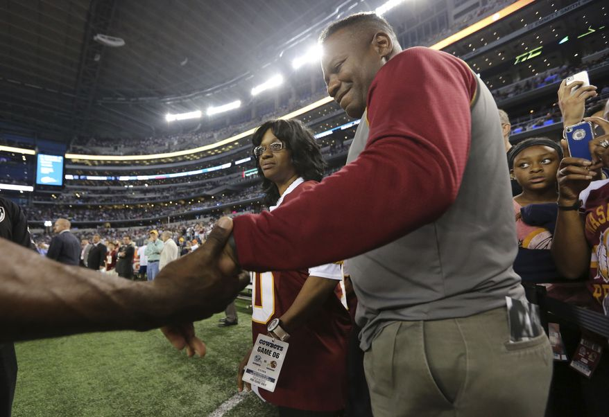 Robert Griffin Jr., right, grapes his son's hand as his wife Jackie Griffin looks on before an NFL football game between the Washington Redskins and Dallas Cowboys Sunday, Oct. 13, 2013, in Arlington, Texas. (AP Photo/LM Otero)