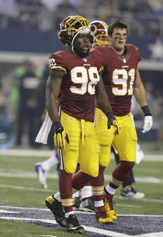 Washington Redskins outside linebacker Brian Orakpo (98) and Ryan Kerrigan (91) walk off the field after an NFL football game Sunday, Oct. 13, 2013, in Arlington, Texas. (AP Photo/LM Otero)