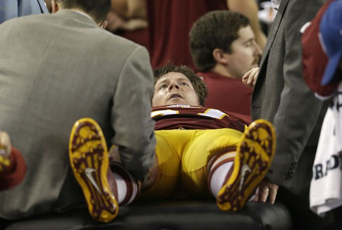 Washington Redskins Nick Sundberg (57) is worked by team staff during the second half of an NFL football game against the Dallas Cowboys Sunday, Oct. 13, 2013, in Arlington, Texas. (AP Photo/LM Otero)
