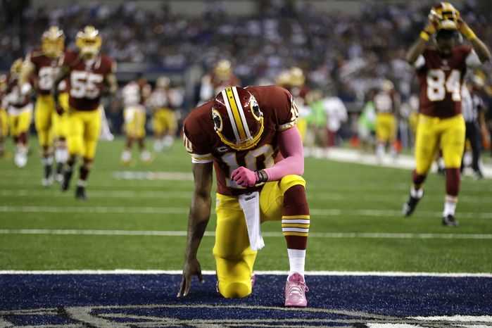 Washington Redskins quarterback Robert Griffin III (10) takes a knee in the end zone before an NFL football game against the Dallas Cowboys, Sunday, Oct. 13, 2013, in Arlington, Texas. The Cowboys won 31-16.(AP Photo/LM Otero)